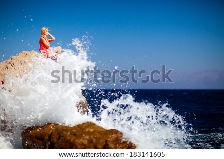 girl on the rock in the sea - stock photo