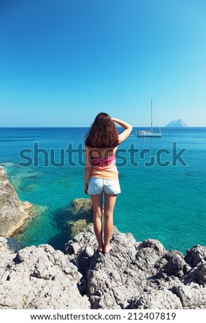 Girl on the rock looking to the horizon - stock photo