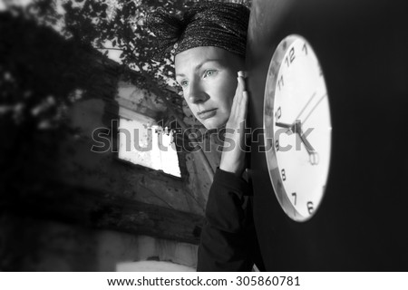 Girl on the ruins of the house with a huge clock in his hands. The symbolism of the time, the transience of life.