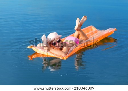 girl on the swimming mattress reading a book - stock photo
