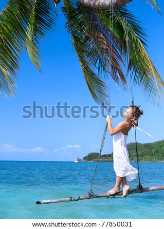 girl on the swing on the beach  in white dress - stock photo