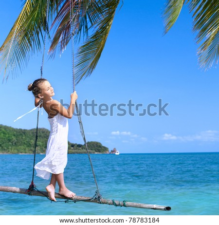 girl on the swing on the beach  in white dress