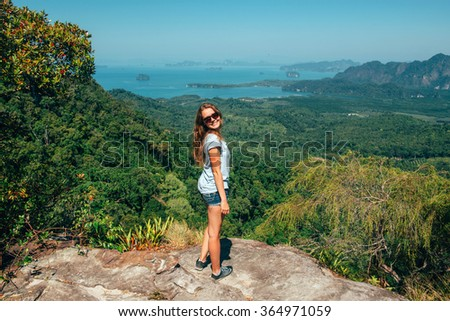 Girl on the view point of the mountain happy, smiling to the camera. Traveler enjoying the landscape from mountain in Tab Kak Hang Nak Nature Trail, Krabi, Thailand