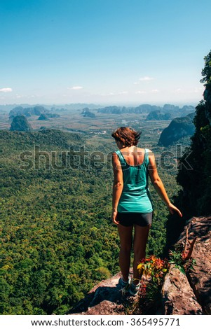 Girl on the view point of the mountain, standing back in front of camera and looking down. Traveler enjoying the landscape from mountain in Tab Kak Hang Nak Nature Trail, Krabi, Thailand