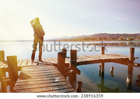 Girl on the wooden jetty at a lake - stock photo