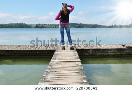 Girl on the wooden jetty. Switzerland - stock photo