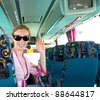 Girl on tourist bus happy with sunglasses with greeting gesture - stock photo