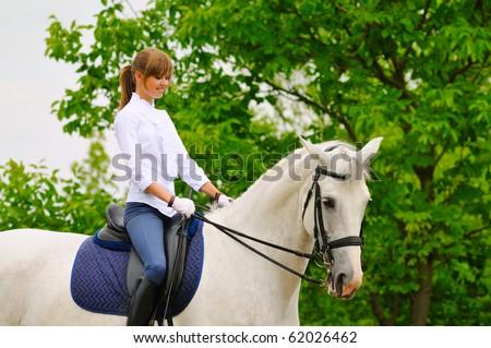 Girl on white dressage horse - stock photo