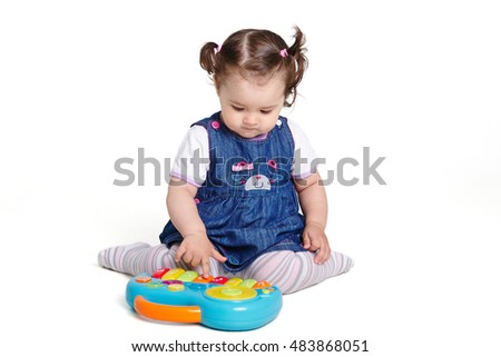 Girl one year playing with a musical toy