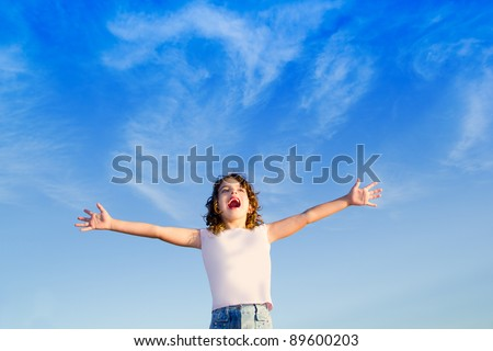 Girl open arms outdoor under blue sky with happiness gesture
