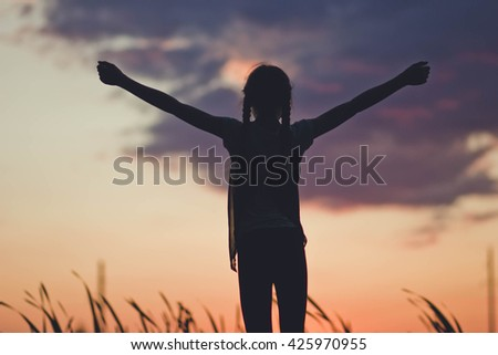 girl open arms under the sunrise at seaside