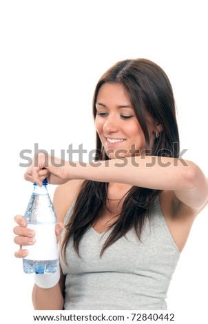 Girl open bottle of drinking mineral water. Female holding in hand blue sparkling still mineral bottled water isolated on a white background. Healthy lifestyle concept - stock photo