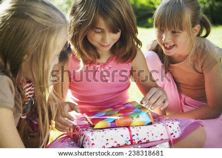 Girl Opening Birthday Presents - stock photo