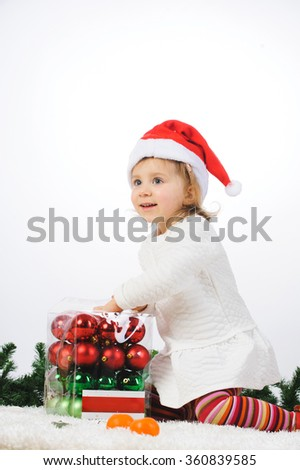girl opening box with christmas balls - stock photo