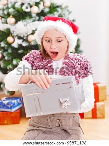 Girl opening Christmas gift box with very surprised facial expression - stock photo