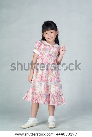 girl or asia little girl doing victory gesture - stock photo