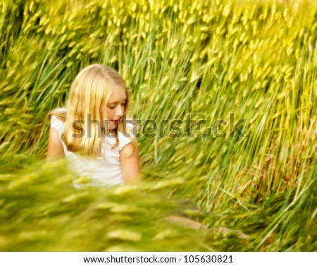 Girl or teen sitting in wheat field looking down - stock photo
