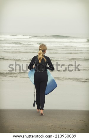 Girl or teen walking in to waves with body board on Rockaway beach Oregon - stock photo