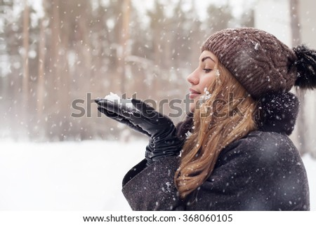 girl outdoor portrait. Winter woman blowing snow in a park, closeup - stock photo