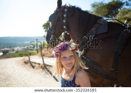 Girl outdoors with a horse on a summer day - stock photo