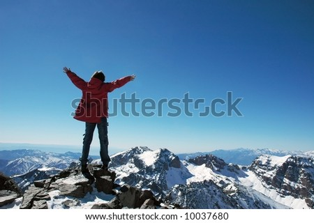 Girl over a snowcapped peaks with outstretched arms - stock photo
