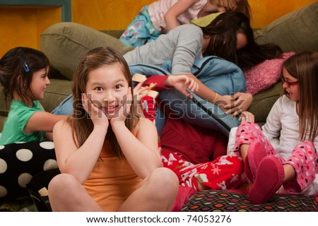 Girl overwhelmed with silly friends at a sleepover - stock photo