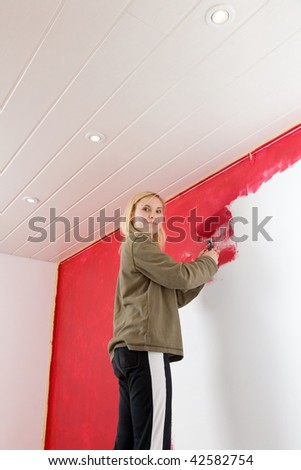 Girl painting a room in red color. - stock photo