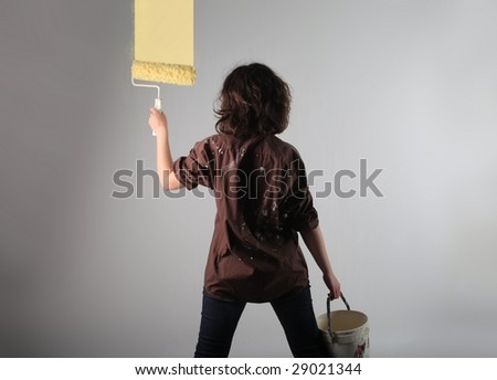 girl painting a wall with a roll - stock photo