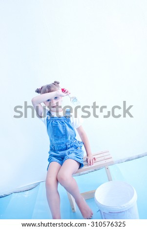 girl painting the wall at home