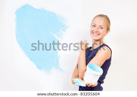 Girl painting the walls in blue - stock photo