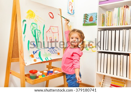 Girl painting with green brush at the easel - stock photo