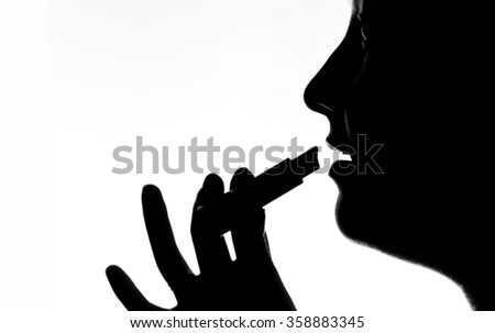 Girl paints her lips with lipstick - black and white silhouette
