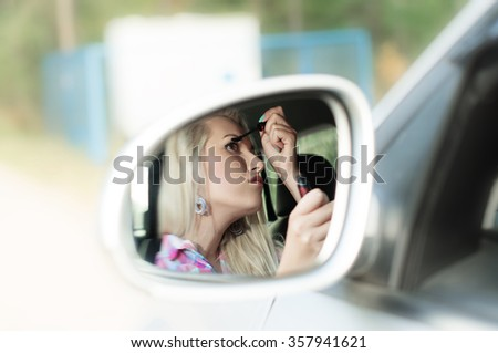 Girl paints the lashes for driving the car in the mirror