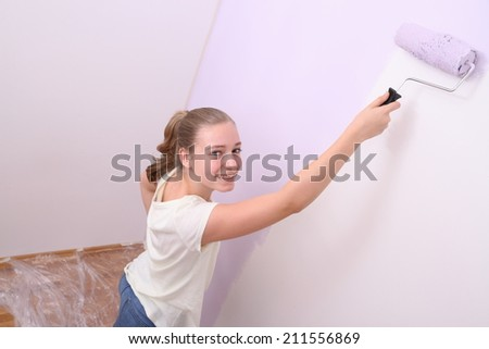 Girl paints wall in lilac color with roller, top view - stock photo