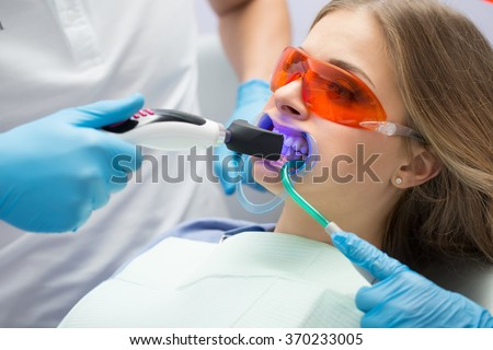 Girl patient in the dental clinic. Teeth whitening UV lamp with photopolymer composition. - stock photo