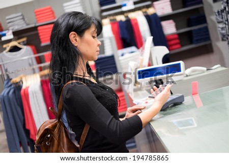Girl pays to shop using mobile phone. NFC - Near field Communication. Mobile payment. - stock photo