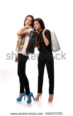 Girl peaking into her friends shopping bag - stock photo