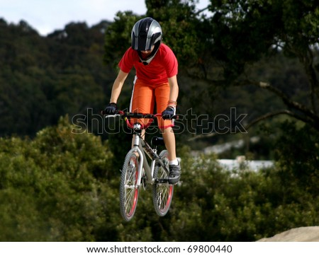 Girl performing a jump on a BMX bike.