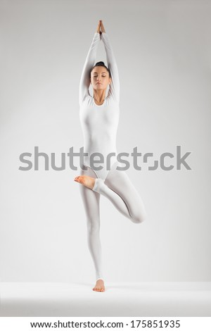 girl performs yoga in white studio - stock photo