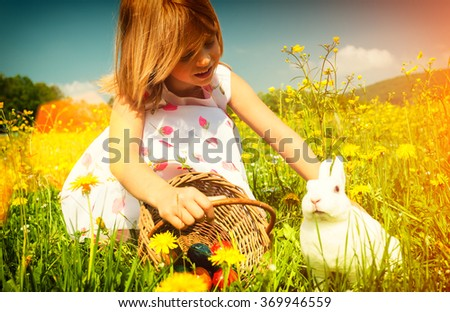 Girl petting Easter bunny on meadow with eggs - filtered image - stock photo