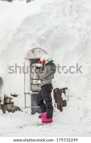 Girl phoning in mountain with heavy snowfall - stock photo