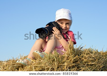 Girl photographer. Little girl sitting on straw with a camera. - stock photo