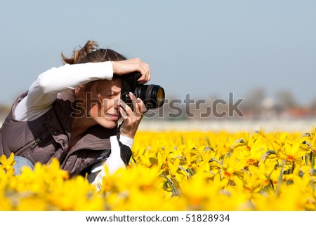 Girl photographer making pictures of flowers. Spring in the Netherlands - stock photo