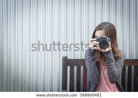Girl Photographer Sitting On Bench and Pointing Camera. - stock photo