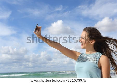 Girl photographing a selfie with a smart phone on the beach enjoying holidays in a sunny day - stock photo