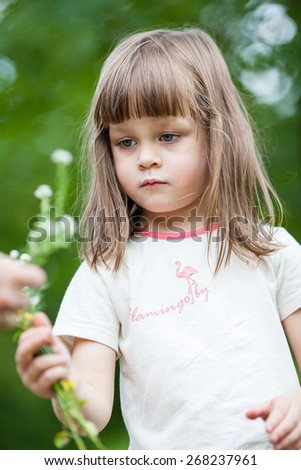 Girl picking flowers. Beautiful little girl picks flowers on a spring green meadow. Shallow depth of field - stock photo