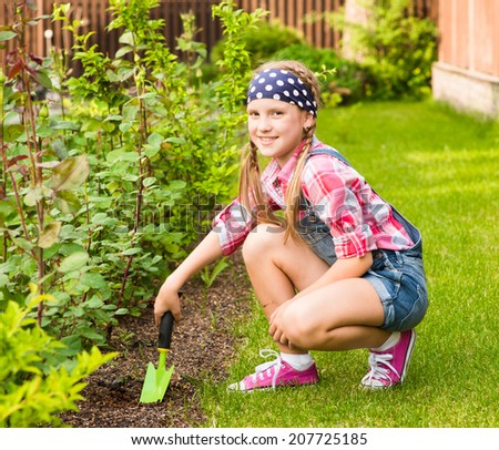 Girl planting plants in the garden - stock photo