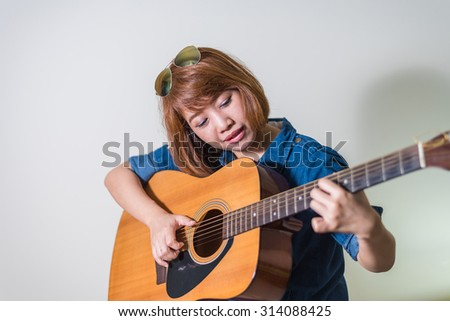 girl playing acoustic guitar isolate on white - stock photo
