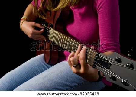 girl playing an electric guitar with black background - stock photo