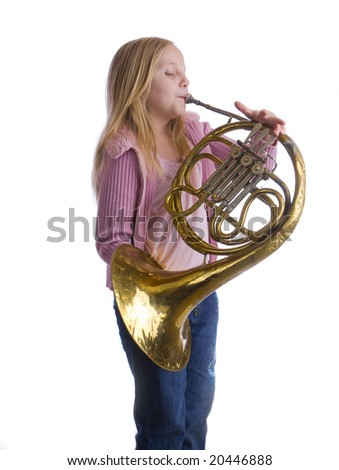 Girl playing an old French horn while standing - stock photo